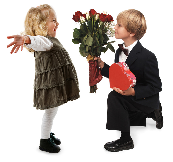 A little boy giving hearts and flowers to a little girl on a white background